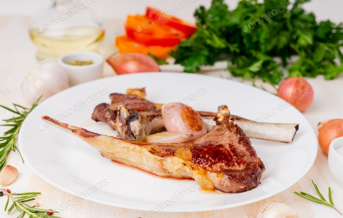 Fat fried lamb ribs, paleo, lchf diet on white plate with vegetable