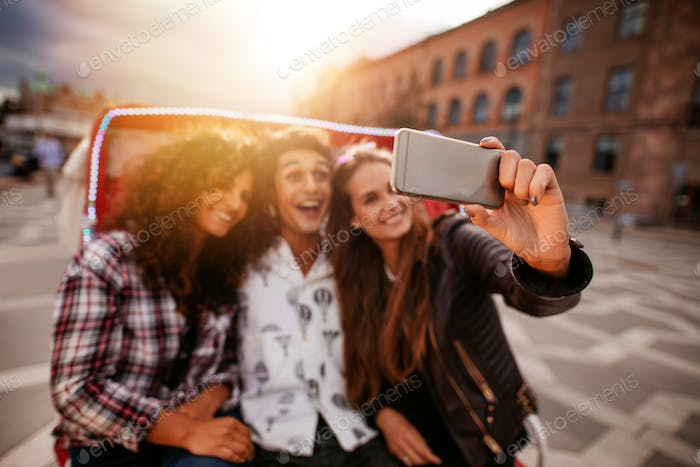 Three young friends taking selfie on tricycle ride.