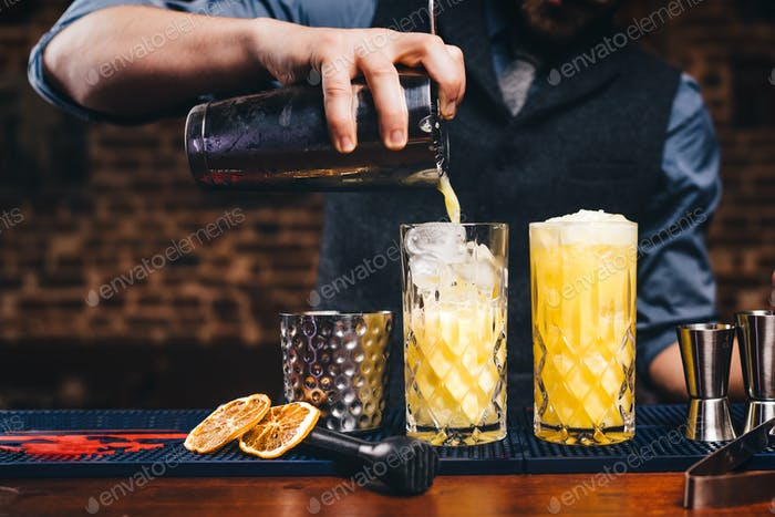 Close up details of working bartender. Pouring citrus cocktail over ice, orange cocktail details