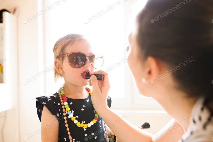 Mother painting lips of her cute little daughter with lipstick.