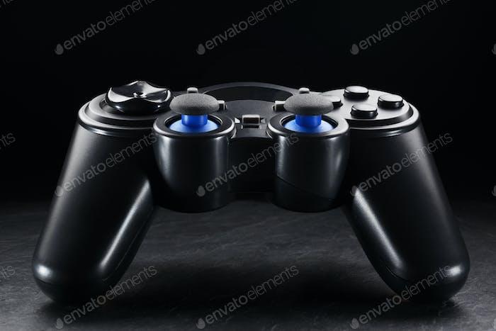 Black wireless gamepad or joystick on black background.