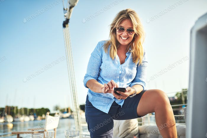 Smiling mature woman using a cellphone on boat deck