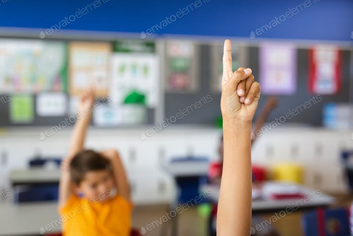 Boy raising his hand for participation in the class at elementary school