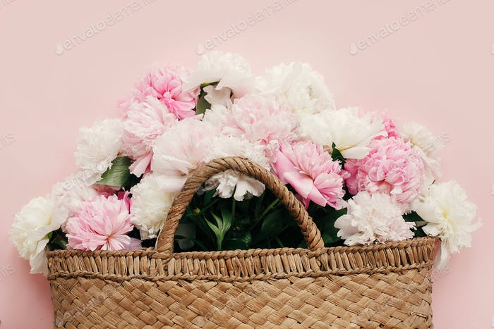 Stylish straw rustic bag with white and pink peonies on pastel pink paper, flat lay