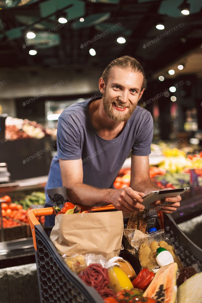 Young smiling guy leaning on trolley full of products joyfully l