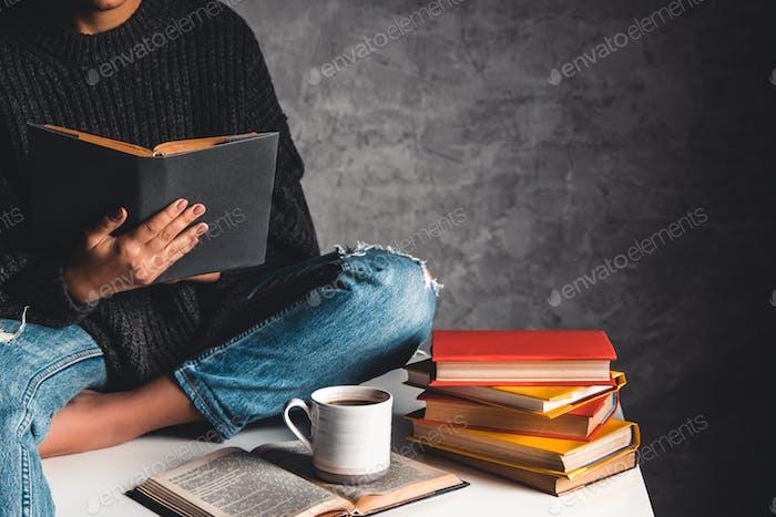 Chica lee libros, estudio, desarrollar con una taza de café en una mesa blanca y un fondo gris