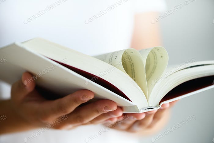 Book with opened pages and shape of heart in girl hands. Copy space. Love concept