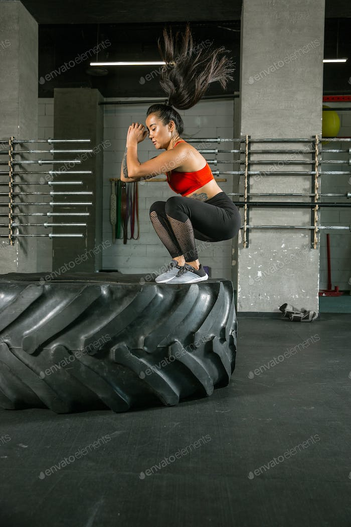 A muscular female athlete doing workout at the gym