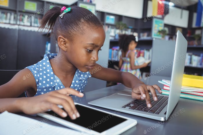 Girl using tablet computer and laptop in library