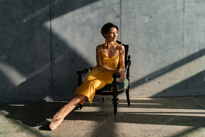 attractive woman in yellow summer dress in interior room concrete wall background