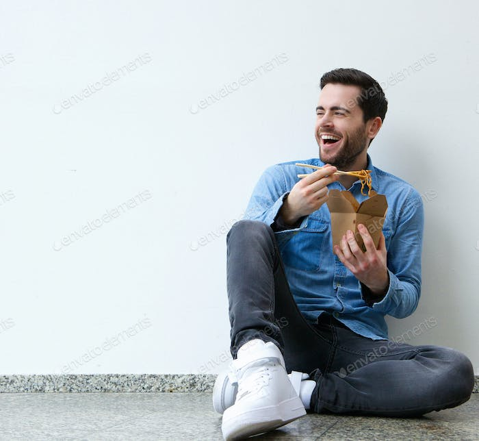 Young man eating chinese food with chopsticks