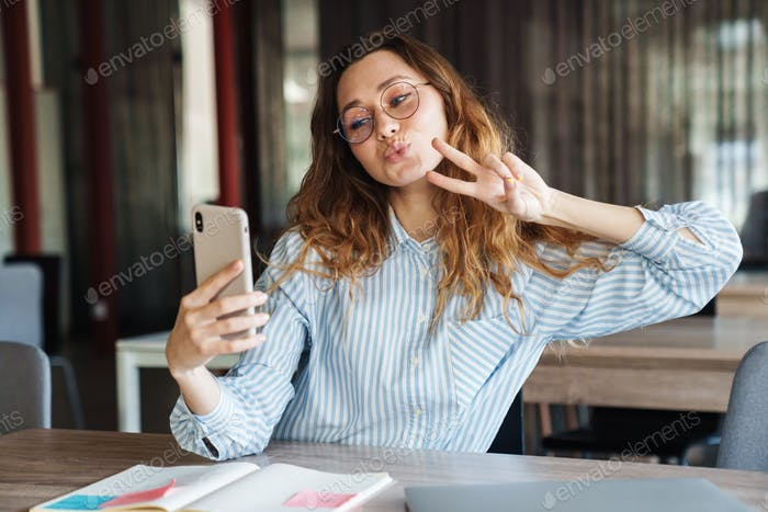 Image of woman gesturing peace sign and taking selfie on cellphone