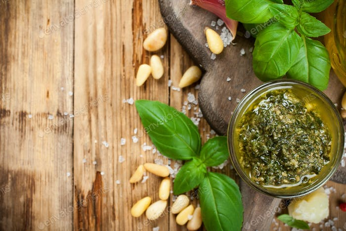 Homemade pesto on a rustic wooden cutting board.