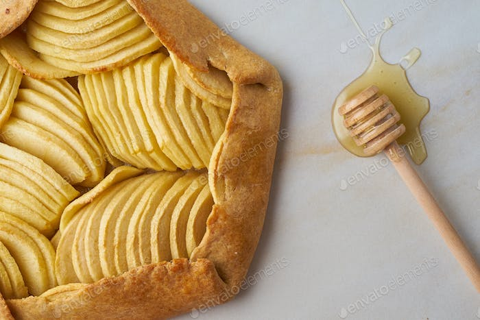 Apple galette, close up pie with a fruits and honey, sweet pastries on marble table, top view