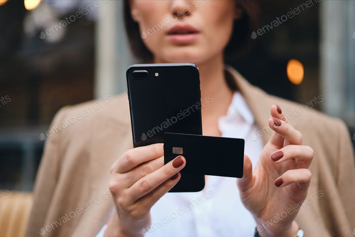 Close up stylish businesswoman with credit card using cellphone outdoor