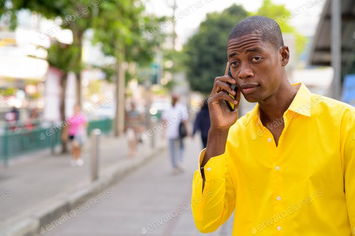 Young bald African businessman talking on phone in the city streets outdoors