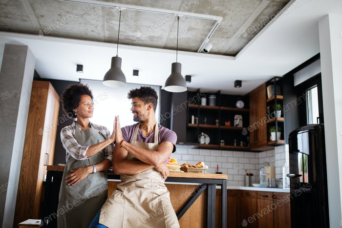Young happy couple in aprons giving high five in kitchen