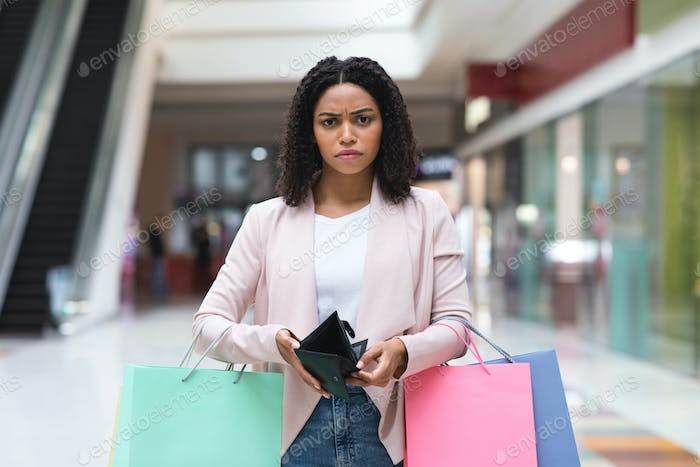 Shopaholism. Upset Black Woman Holding Lots Of Shopping Bags And Empty Wallet