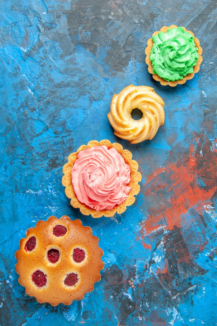 top view diagonal row raspberry cake small tarts biscuit on blue table