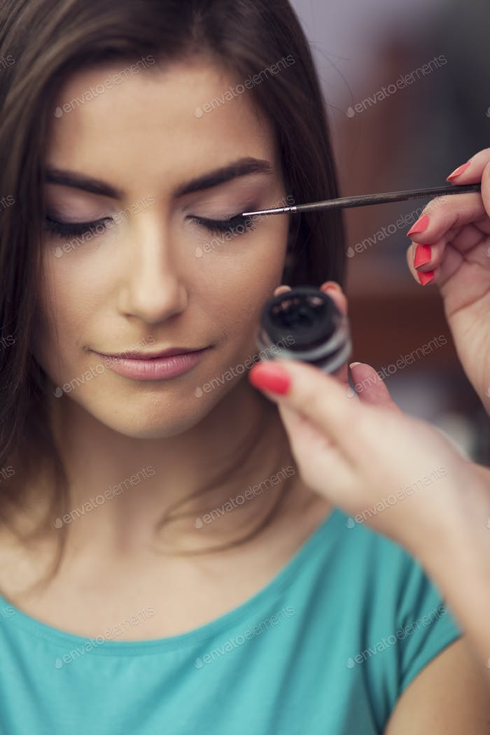 Applying eyeliner from inkwell by makeup brush