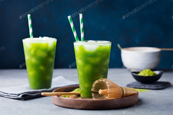 Matcha, Green Tea Ice Tea, Cocktail in tall Glass on Wooden Plate. Grey Stone Background.