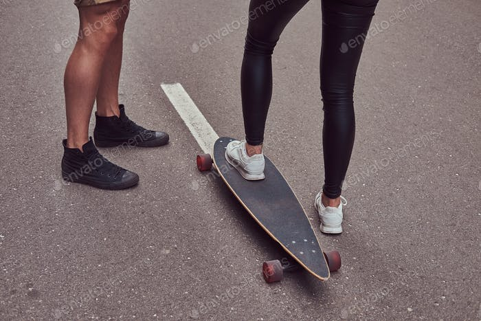 Leisure and sports concept - close-up of teenage couple feet with a longboard on a street.