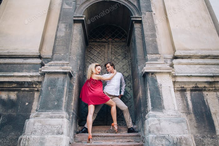 Sexy couple of dancers posing near old wall outdoors