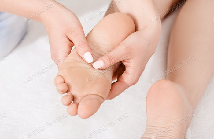 Acupressure of foot. Professional doing massage on white background