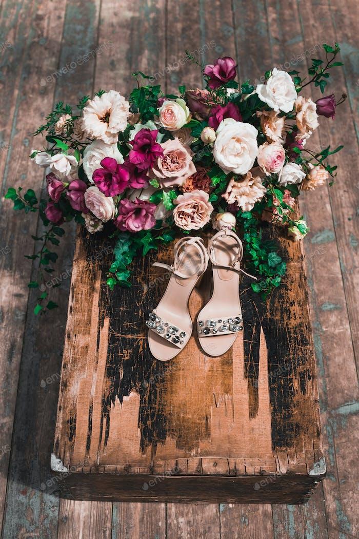 Brautschuhe mit Juwelen und umgeben von Blumenarrangements