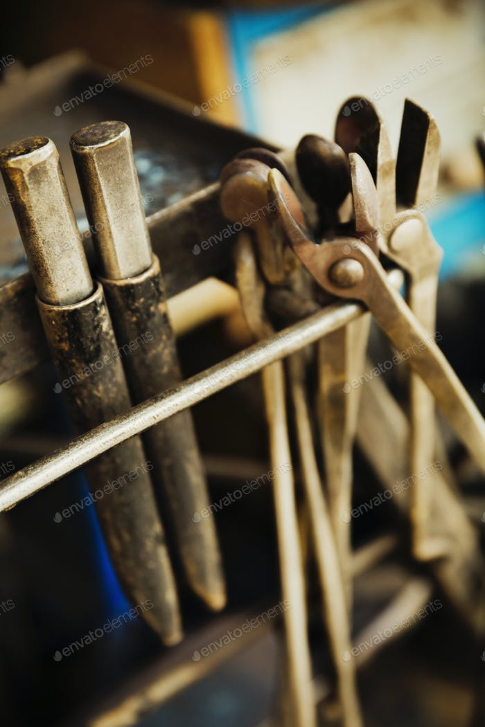 A mobile farrier's crate of work tools, pincers, hammers and metal files.