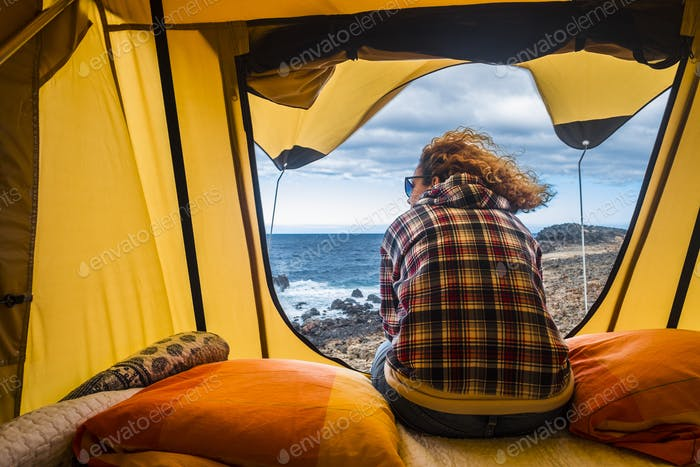 nice woman view from backside sitting inside a tent  in free life camping