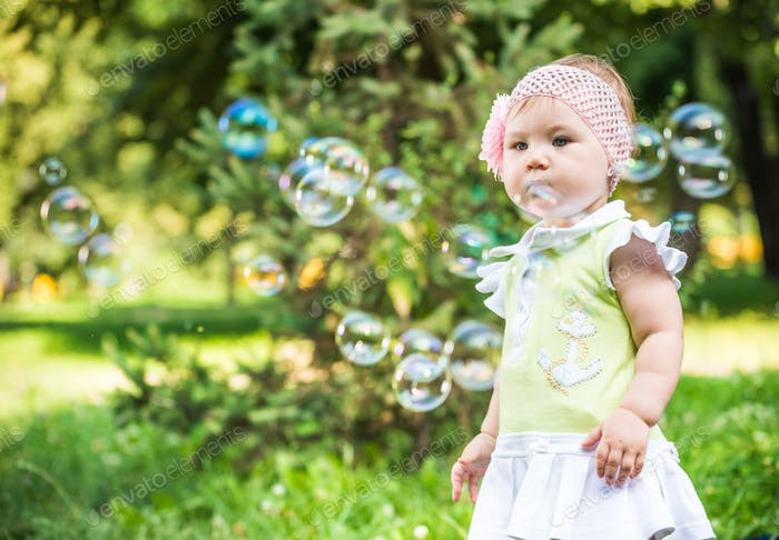 Small baby girl in dress standing and looking at bubbles in air