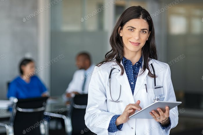 Doctor holding digital tablet at meeting room