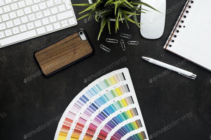 Espacio de trabajo de diseño gráfico con escritorio negro, vista superior