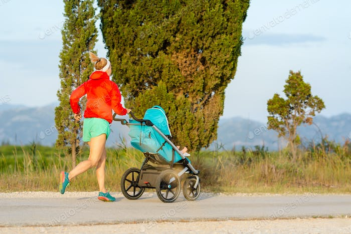 Running mother with stroller enjoying motherhood at sunset lands