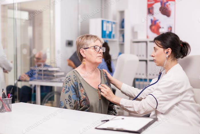 Doctor checking old woman heart beat