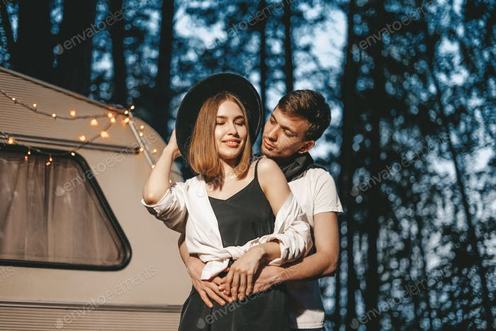Young couple in love in stylish outfit romantic weekend wedding trip against background of camper