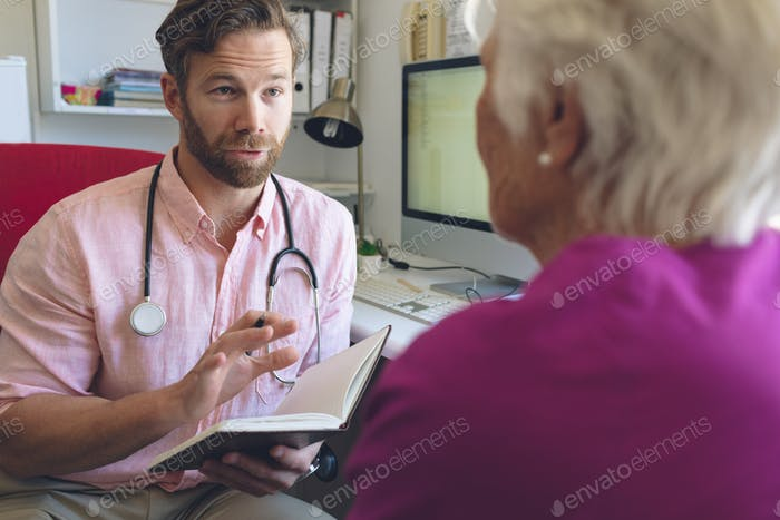 Caucasian male doctor writing prescription on notebook to senior woman