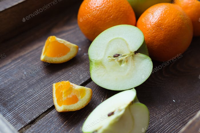 Apple and orange on the wooden tray