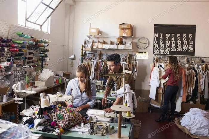 Machinist and colleagues working at a clothing design studio
