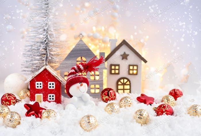 Weihnachtskomposition mit dem Schneemann, Hütten und festlichen Dekorationen