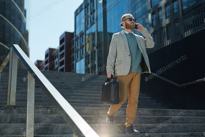 Stylish businessman using phone on move