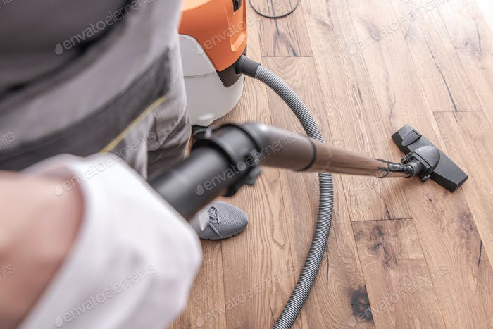 Male Worker Vacuuming Hardwood Flooring.