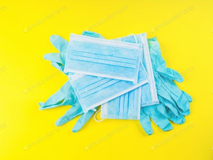 Blauer medizinischer Handschuh und Gesichtsmasken auf gelb. Covid