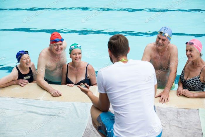 Männliche Instruktor Unterstützung Seniorenschwimmer am Pool