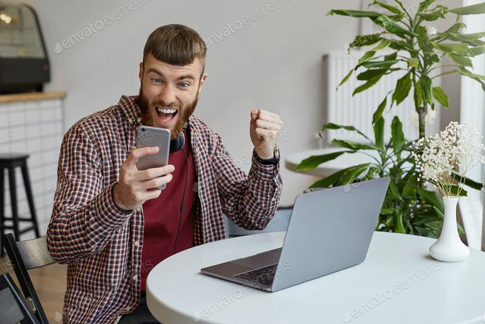 Young attractive ginger bearded man sits at a table in a cafe and works