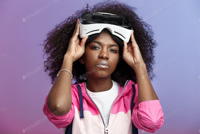 Mod curly brown-haired girl dressed in the pink sports jacket wearing on her head the virtual
