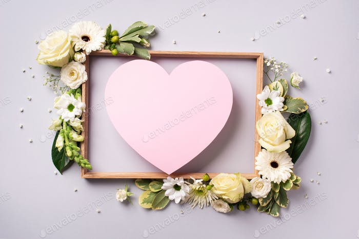 Creative layout with pink flowers, paper heart over grey background. Top view, flat lay. Spring