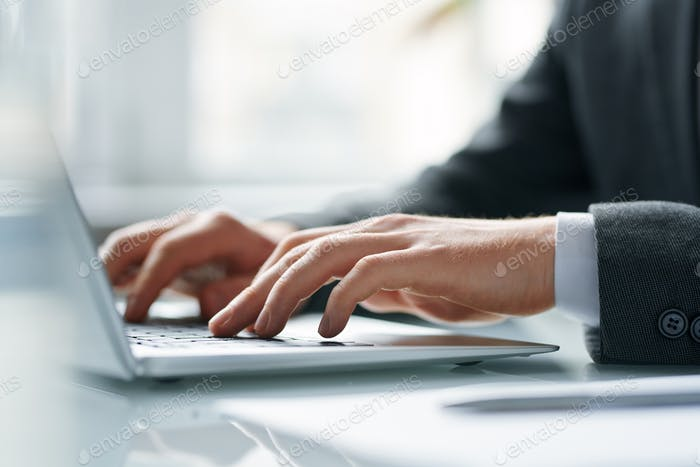 Hands of contemporary mobile broker pushing keys of laptop keypad