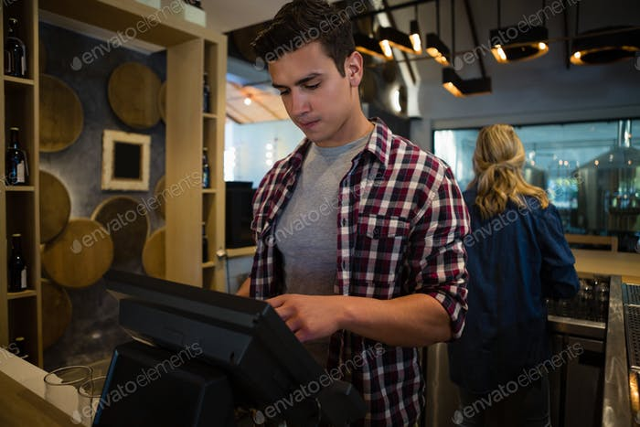 Hombre Uso caja registradora en el bar